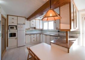 Cocina con muebles y mesa blanca