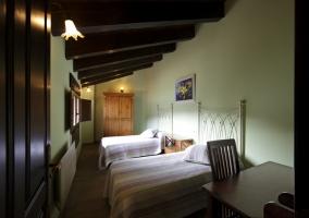 Habitación con 2 camas y mesa con silla de la casa rural
