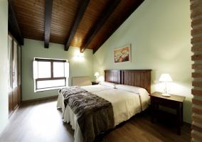 Habitación con 2 camas juntas y suelo y techos de madera de casa rural