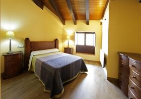 Habitación con cama matrimonial y paredes amarillas