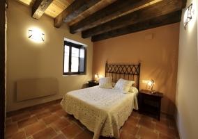 Habitación con cama matrimonial y techos de madera