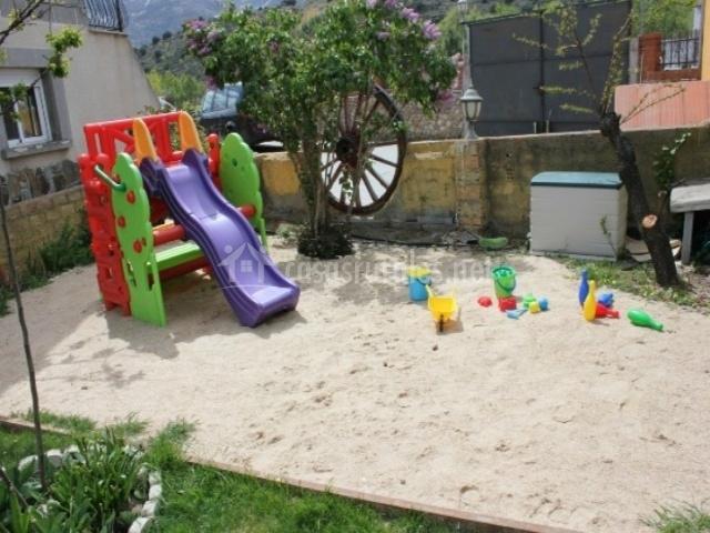 Jardín con juegos para niños y arena