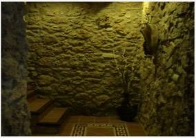 Salón con maderos en el techo y pared de piedra de casa rural