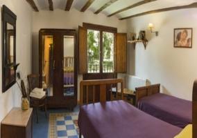 Dormitorio doble con mobiliario de madera y amplio balcón