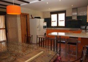 Cocina con detalles en madera y mesa de trilla