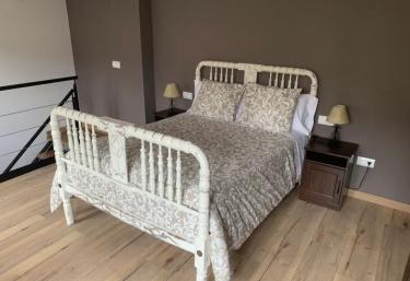 Dormitorio de matrimonio con suelos de madera y mesillas de noche