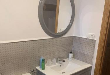 Un aseo en color gris con espejo redondo
