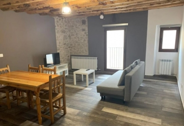 Sala de estar amplia en tonos grises con mesa de madera