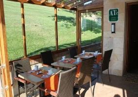 Porche en entorno muy soleado con varias mesas para comer en la mejor atmósfera