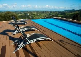 Amplia piscina con sus sillas para que tomes el sol