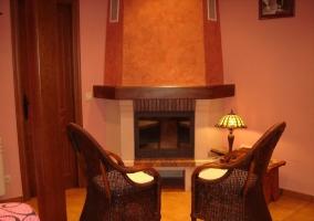 Sillón de color rosa con estampado negro frente al televisor