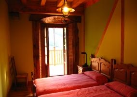 Dormitorio con dos camas y balcón
