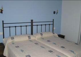 Habitación con 2 camas y pared de fondo azul