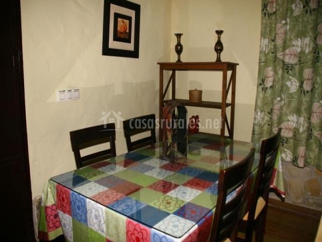 Mesa de comedor con cristal encima y mantel de flores
