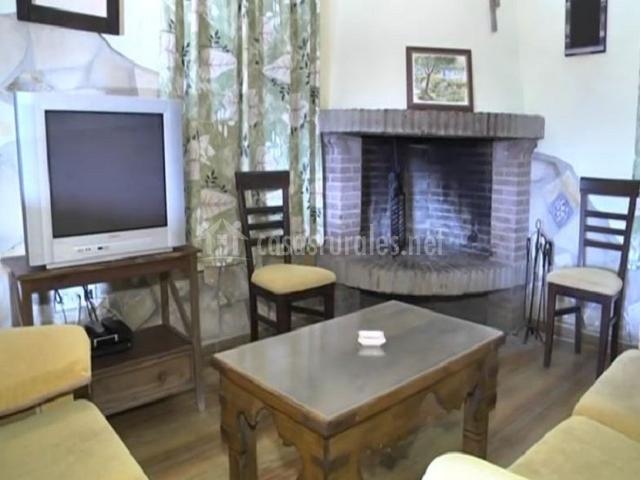 Salón con chimenea de ladrillos junto al televisor