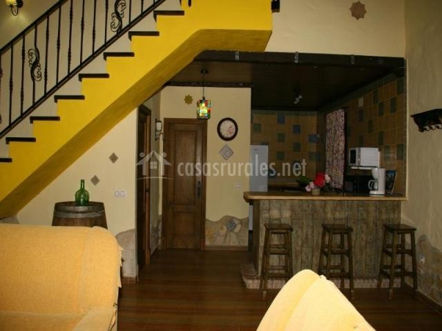 Salón de la casa con barra americana y la cocina