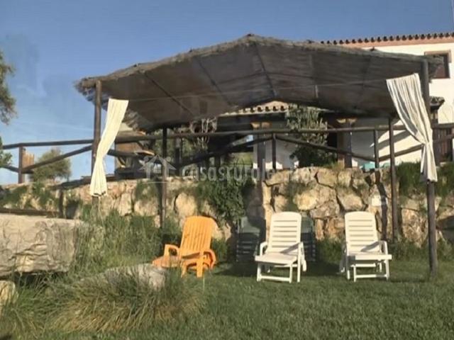 Zona techada con tumbonas junto a la piscina