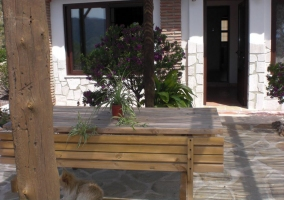 Detalle de la mesa y bancos de madera en el porche de la casa rural