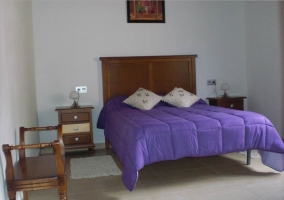 Dormitorio con colcha morada y cabecero de madera en la casa rural