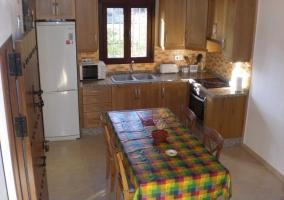 Vista de la cocina con muebles de madera y mesa de comer en la casa rural