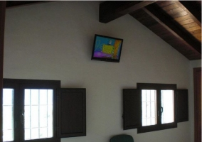 Televisor en la pared de un dormitorio de la casa rural