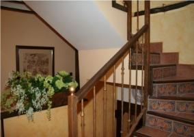 Escaleras de la casa rural y maceta con flores