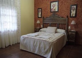 Dormitorio con una pared con estampados y otra en tono vainilla