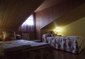 Dormitorio doble abuhardillado en maderd y con la luz encendida