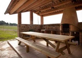 Zona de barbacoa con mesa y bancos de madera