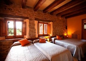 Habitación con 3 camas y cojines naranja
