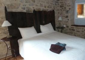 Habitación con paredes de piedra y cabeceros de madera