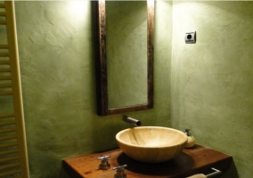 Lavabo con pila redonda color beige y pared verde