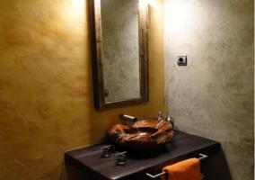 Lavabo con pila de madera y espejo vertical