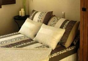 Dormitorio de matrimonio con cojines de color crudo