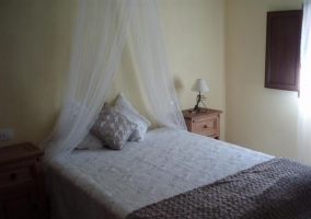 Dormitorio de matrimonio con manta en tonos grises