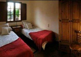 Dormitorio doble con mantas de color rojo