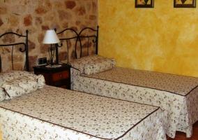 Habitación con cama de matrimonio y sabanas bordadas
