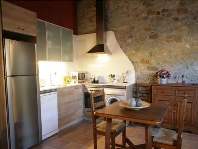 Cocina con mesa de comedor y muros de piedra