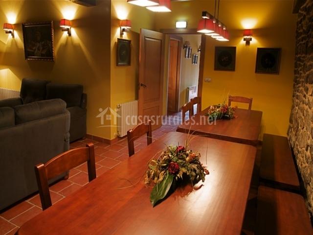 Comedor con bancos y sillas en el salón de la casa rural