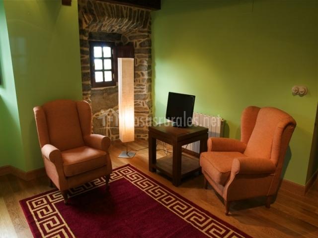 Dormitorio de matrimonio con salita de descanso y tele en la casa rural