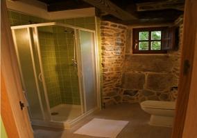 Aseo con ducha en la casa rural y paredes de piedra