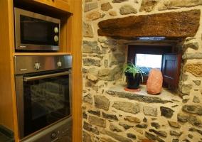 Cocina con electrodomésticos y ventanuco en la casa rural