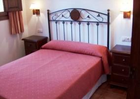 Dormitorio de matrimonio con colcha granate y dos mesitas de noche