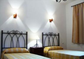 Dormitorio doble de con colchas de cuadros en tono amarillo de la casa rural