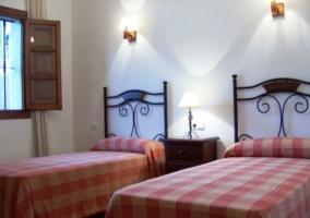 Dormitorio doble con colchas de cuadros y una mesita en la casa rural