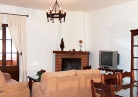 Salón con chimenea y televisor de la casa rural malagueña