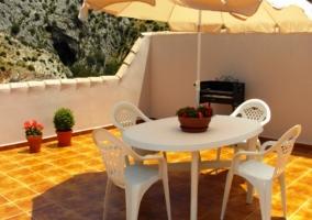 Terraza de la casa rural con mesa, sillas y sombrilla