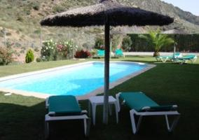 Tumbonas y piscina de la casa rural