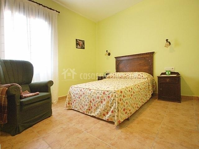 Habitación con cama de matrimonio amarilla