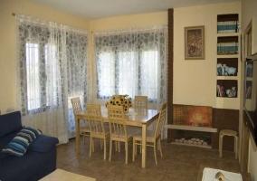 Salón-comedor con mesa y chimenea de leña